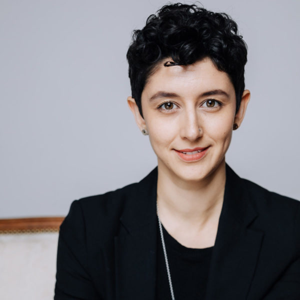Gillian Cofsky smiles in a white, airy room. Gillian wears a black blazer over a black shirt, and a long, thin, silver necklace.