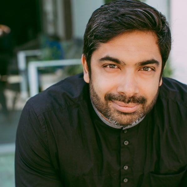Sirish Rao has short black hair, a tight black beard, and is wearing a black shirt. Sirish is leaning forwards and smiling.