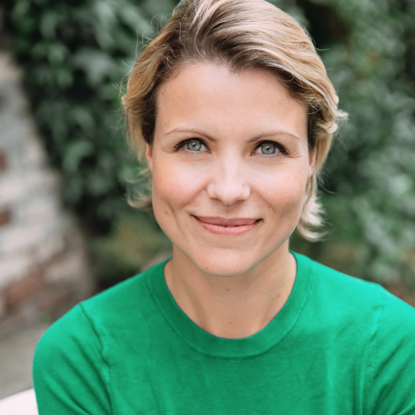 Laura Byspalko is wearing a bright kelly green shirt, chin length blonde hair swept back.