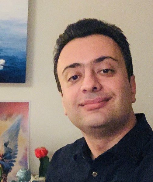Khalil Chahian Borujeni smiles at the camera, head tilting to the left. Khalil has cropped black hair and wears a navy button up shirt.